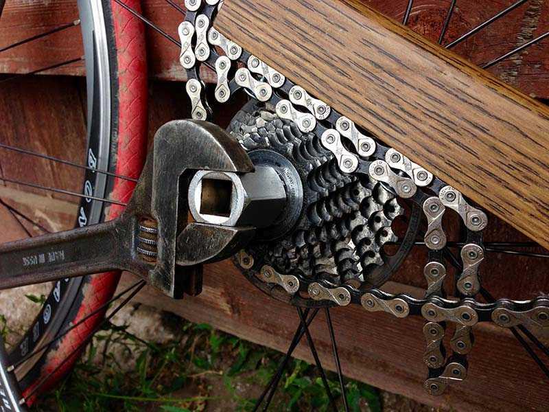 Снятие кассеты задних звездочек с заднего колеса горного велосипеда при помощи двух съемников и разводного ключа