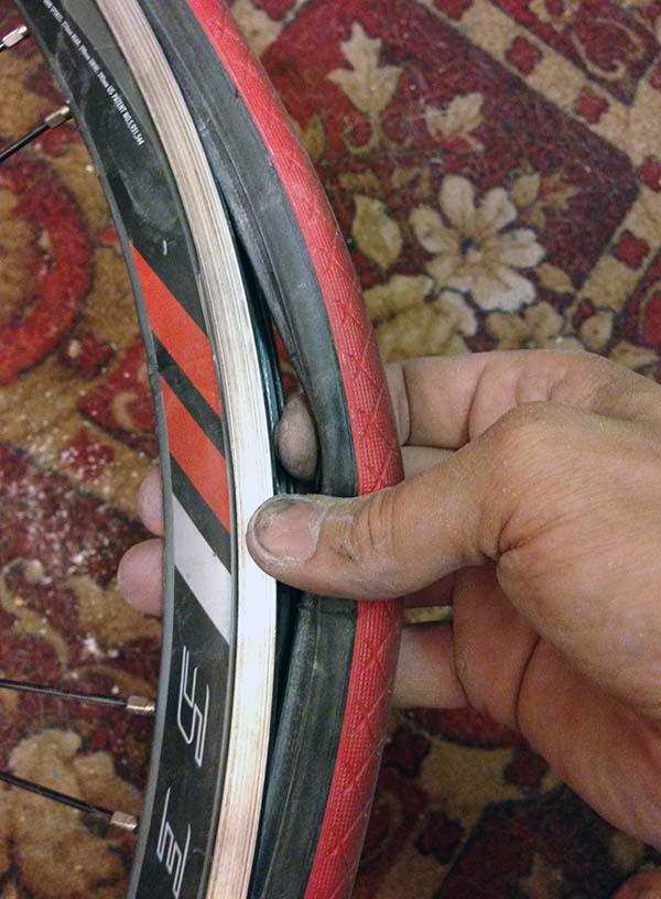 Оттягиваем покрышку велосипеда с противоположной стороны соска
