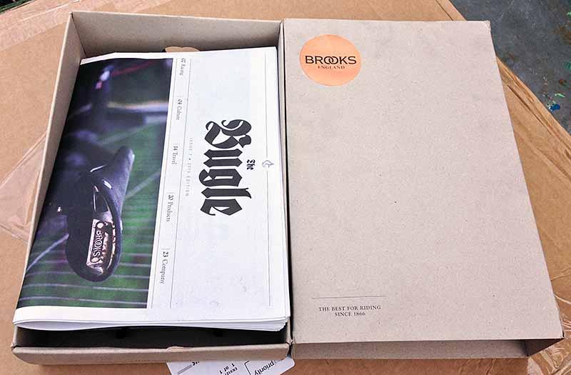 В коробке с велосипедным седлом Brooks Team Pro Chrome обнаружилась подарочная газета The Bugle